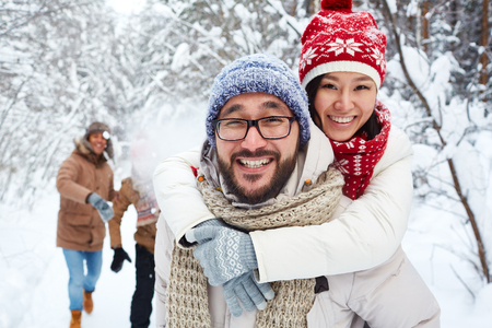 winter vacation: Portrait of smiling young couple walking in the forest with friends