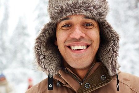 hombre con sombrero: Retrato de hombre joven en sombrero de piel sonriendo a la cámara