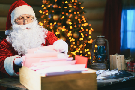 holiday tradition: Concentrated Santa Claus sitting and checking his Christmas lists Stock Photo