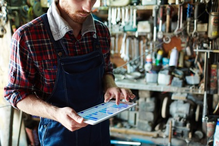 manufacture: Repairman checking earning record on touchpad Stock Photo