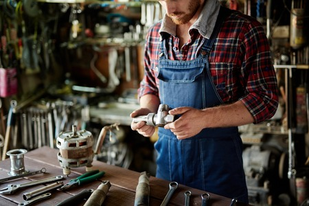 spare part: Plumber looking at spare part in his workshop Stock Photo