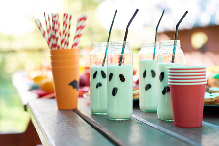 Milk in long jars with straws and plastic glasses on wooden table Stock Photo