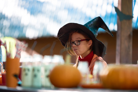 youthful: Youthful girl in witch hat sitting by festive table Stock Photo