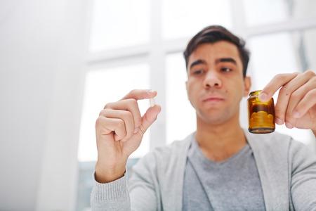 addicted: Drug addicted guy holding pill