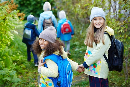 Two happy girls with backpacks looking at camera while walking to school Stock Photo