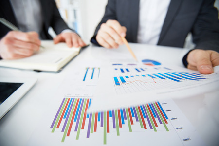 discussed: Financial charts on papers being discussed by men Stock Photo
