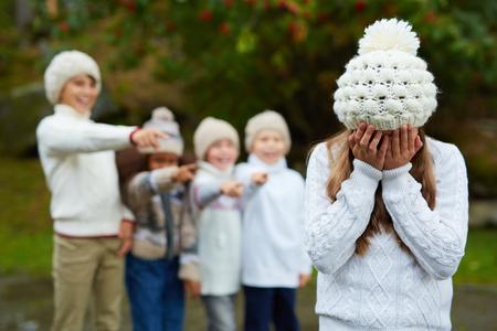 conflictos sociales: Malestar niña llorando mientras que el grupo de niños de su intimidación