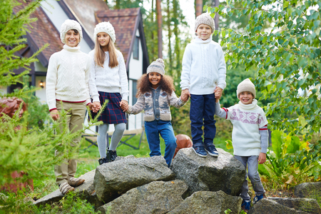 schoolmate: Happy kids in knitted caps and sweaters standing on stones Stock Photo