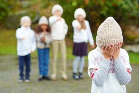 conflictos sociales: El pequeño niño llorando con el rostro entre las manos en el fondo de los niños de intimidación