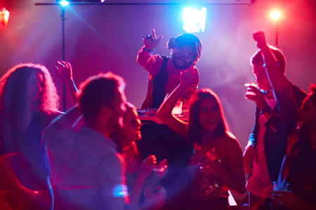 adult entertainment: Ecstatic deejay enjoying disco party while young people dancing near by Stock Photo