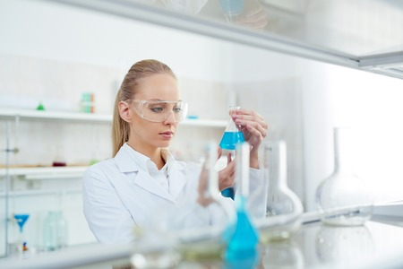 laboratory research: Young female testing new substance in chemistry lab