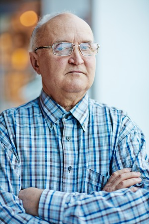 elderly adults: Retired cross-armed man looking at camera Stock Photo