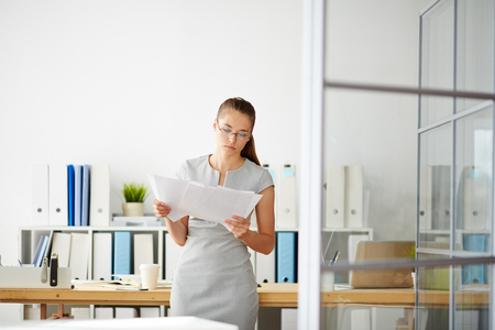 woman work: Serious young woman looking through papers in office