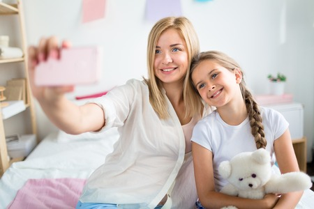 blonde mom: Mother and daughter making selfie at home