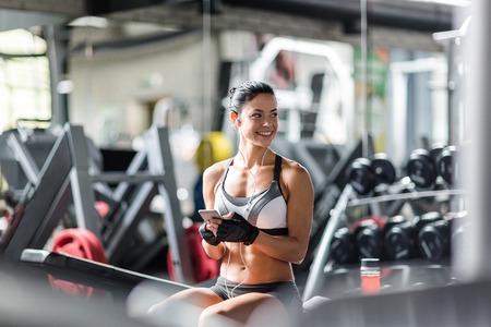 la mujer del ajuste se escucha música en el gimnasio sonriendo