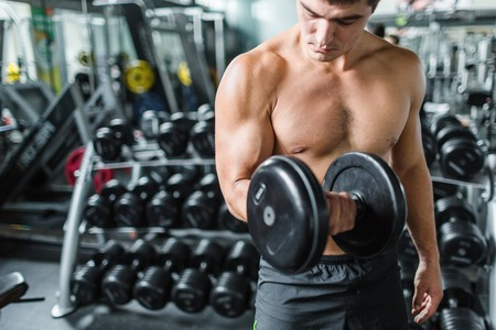 Muscular man exercising with barbell in gym Stock Photo