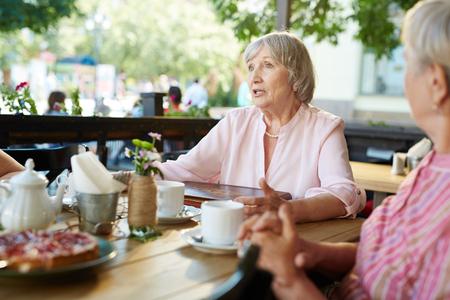 senior women: Grey-haired female telling something to her friends
