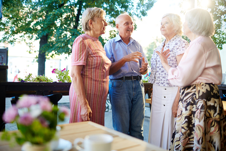 Mature friends having conversation in outdoor cafe at leisure