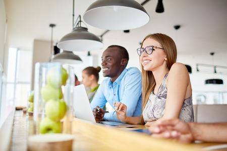 cafe internet: Muchacha creativa y sus colegas de trabajo en el café internet