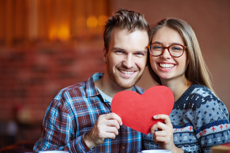 amorous: Amorous couple with red paper heart looking at camera Stock Photo