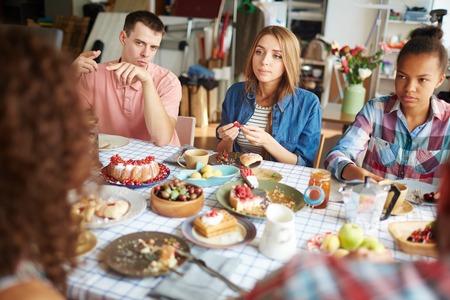 amigas conversando: los jóvenes amistosos que tienen conversación de la cena festiva