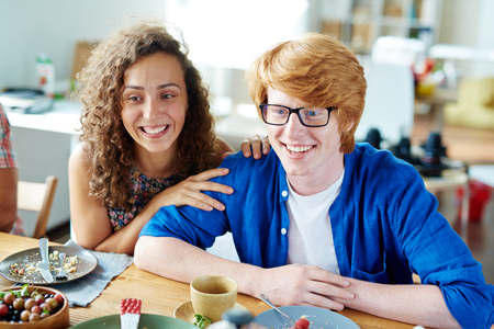 Happy young couple talking to friends by festive table