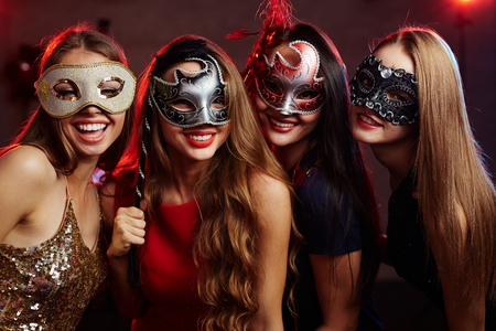masquerade masks: Group of happy girls in masquerade masks having party
