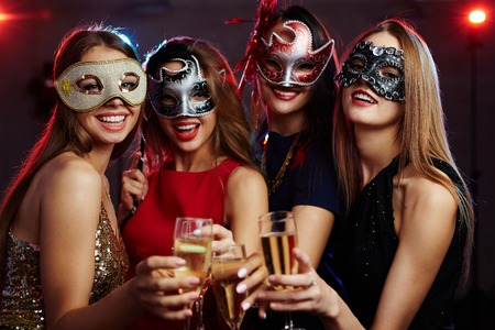 Girls in masks toasting with champagne at party