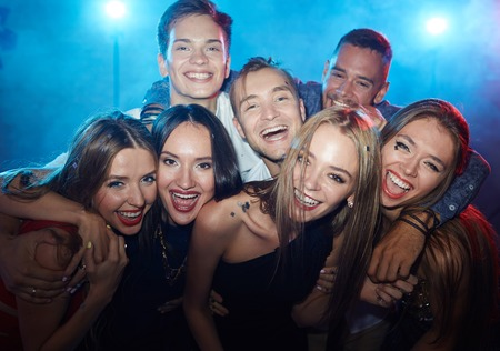 ecstatic: Group of ecstatic friends laughing at party in nightclub