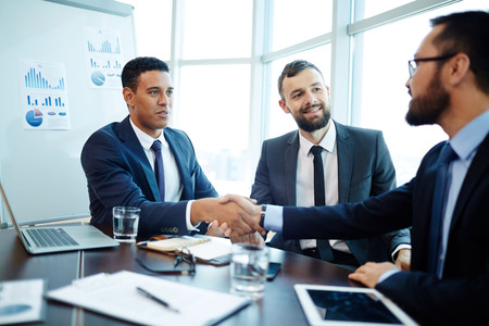 businesspeople: Handshaking business partners after negotiations