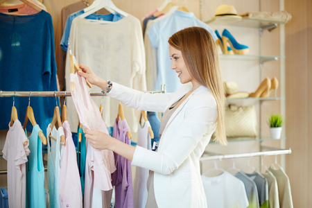shopaholism: Happy shopper looking for new clothes in boutique