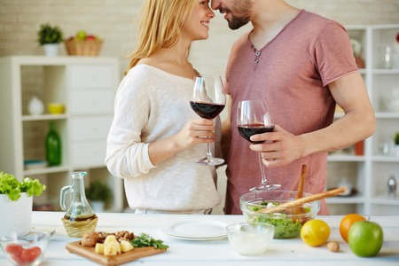 Couple with red wine standing by table in the kitchen Stock Photo