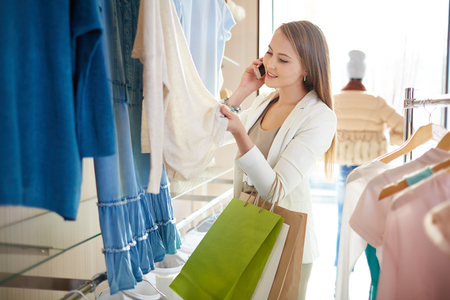 paperbags: Young shopper with paperbags talking on mobile phone while choosing new clothes in boutique Stock Photo