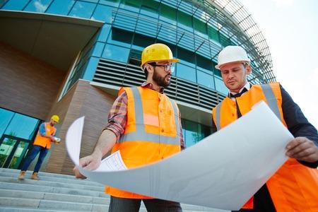 supervisores: Dos supervisores de cascos mirando boceto en plano