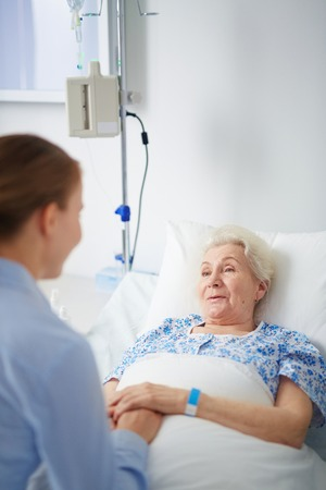elderly adults: Sick woman lying in bed and talking to her granddaughter in hospital Stock Photo