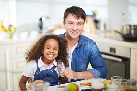 Caucasian man and his African-american daughter having breakfast at home