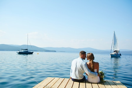 Romantic newlyweds sitting by water