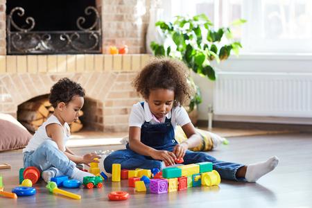 siblings: Two adorable siblings playing on the floor