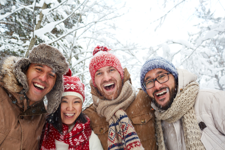 snowfalls: Happy friends enjoying winter day with snowfall