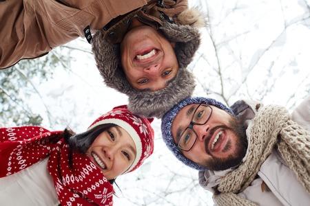 winterwear: Ecstatic friends in winterwear looking at camera outdoors