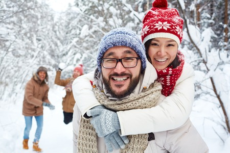Amorous Asian couple on background of their friends playing snowballs on winter day