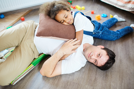 foster: Young father and his daughter playing on the floor Stock Photo