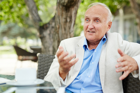 Senior man uit te leggen zijn mening in de buitenlucht cafe Stockfoto
