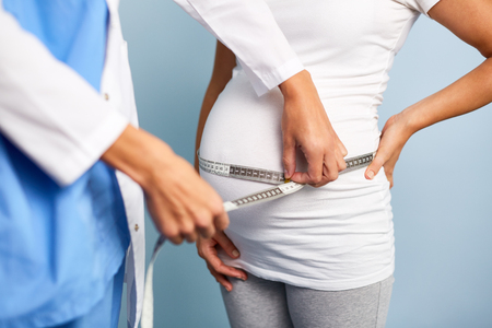 obstetrician: Obstetrician measuring pregnant belly of patient