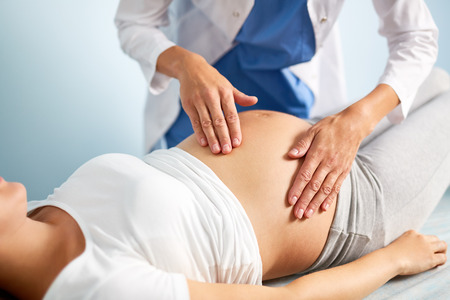 Young pregnant woman having examination of her belly