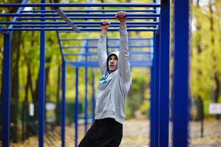Young sportsman doing physical exercises in park Stock Photo