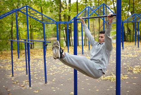 pullups: Sportsman doing pull-ups on horizontal bar in park