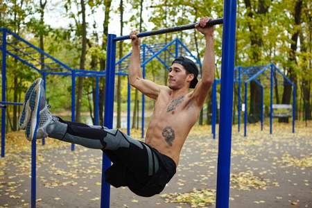 pullups: Shirtless sportsman doing pull-ups on horizontal bar Stock Photo