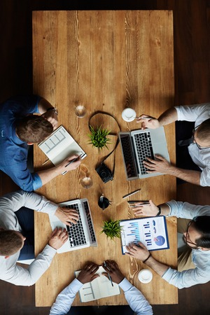 business people meeting: Team of businessmen sitting by table and having meeting Stock Photo