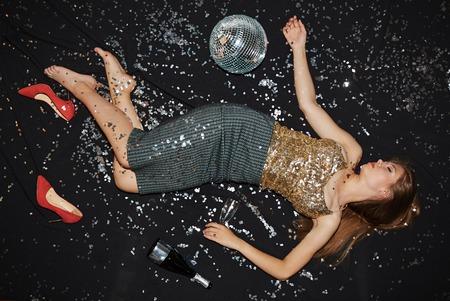 Fille ivre avec une bouteille vide et de la flûte de dormir sur le plancher de danse Banque d'images
